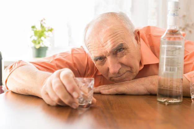 Close-up idosos bêbados segurando um copo pequeno na mesa de madeira com vodka enquanto olha para a câmera.