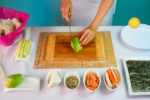 Close-up imagens das mãos da jovem cortando abacate