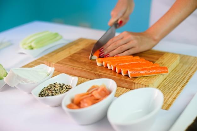 Close-up imagens das mãos da jovem, cortar varas de caranguejo