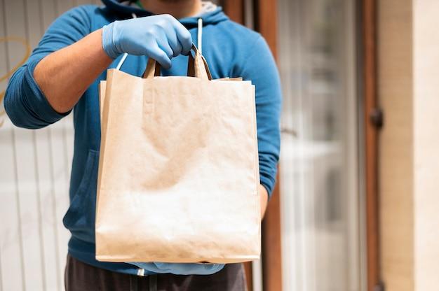 Close-up individual entregando sacola de compras