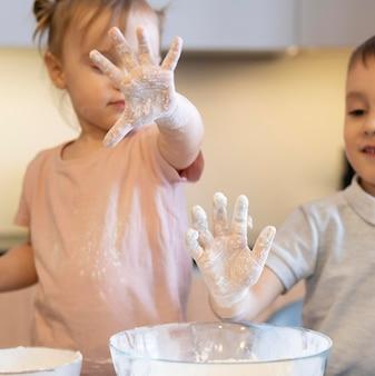 Close-up infantil com farinha nas mãos