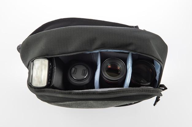 Close-up isolado da foto do estúdio de um pequeno saco com zíper de tecido impermeável à prova de água para fotógrafo profissional preto e cinza contém flash e lente em divisor de compartimento macio no fundo branco.