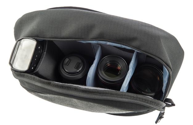 Close-up isolado da foto do estúdio de um pequeno saco com zíper de tecido impermeável à prova de choque para fotógrafo profissional preto e cinza contém flash e lente em divisória de compartimento macio no fundo branco.