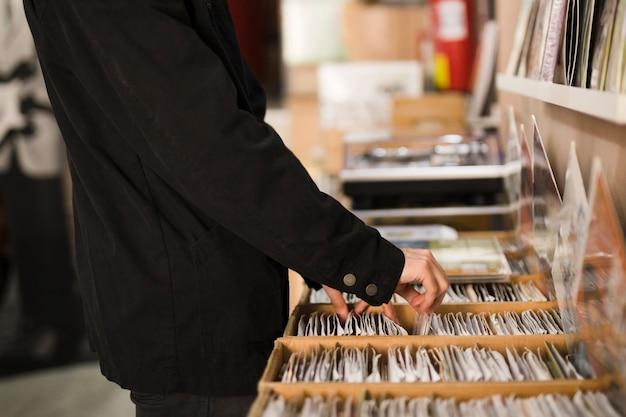 Close-up jovem à procura de vinis na loja