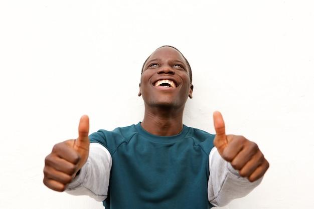 Close-up jovem africano mostrando polegares para cima com as duas mãos no fundo branco