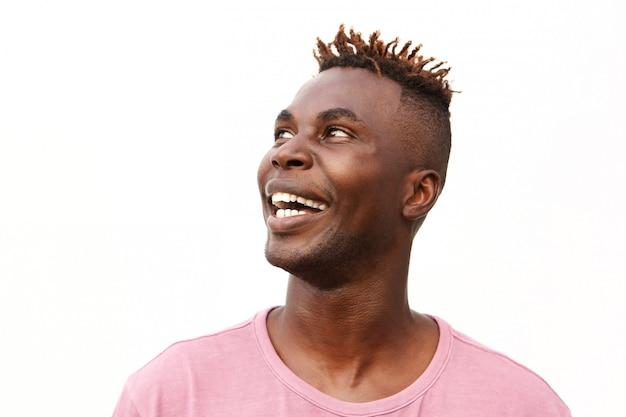 Close-up jovem afro americano olhando para longe e sorrindo contra fundo branco