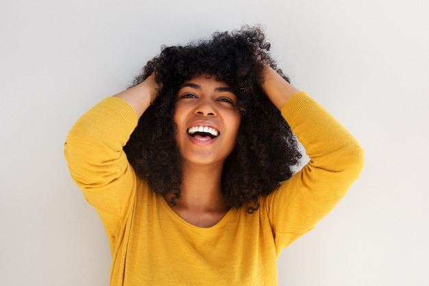 Close-up jovem alegre americana africano rindo com as mãos no cabelo encaracolado