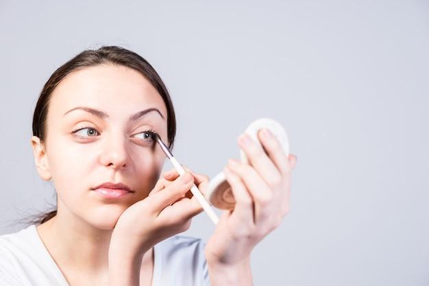Close-up jovem aplicando maquiagem eyeliner enquanto olha para o pequeno espelho de um kit de base em um fundo cinza.