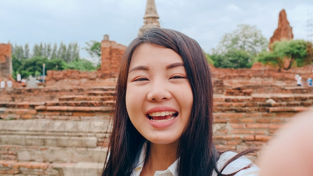 Close-up jovem asiática mochileira blogueira olhando para frente no smartphone