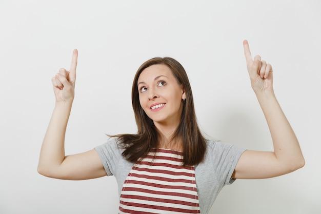 Close-up jovem atraente sorridente morena caucasiana dona de casa no avental isolado. bela governanta apontando o dedo indicador para cima, olhando para cima