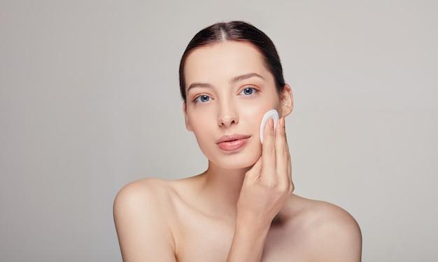 Close-up jovem bonita concurso calma mulher com uma almofada de algodão na mão direita parece reta com olhos azuis no
