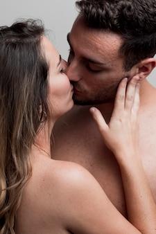 Close-up jovem casal nu beijando