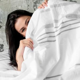 Close-up jovem cobrindo-se com cobertor