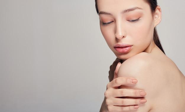 Close-up jovem concurso mulher bonita com total calma e beleza segura a mão esquerda no ombro