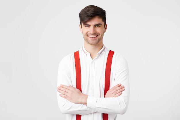 Close-up jovem empresário de cabelo escuro com a barba por fazer em pé com os braços cruzados, vestindo uma camisa branca, suspensórios vermelhos, sorrindo