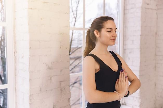 Close-up jovem fazendo ioga sozinha no estúdio de ioga perto da janela de manhã