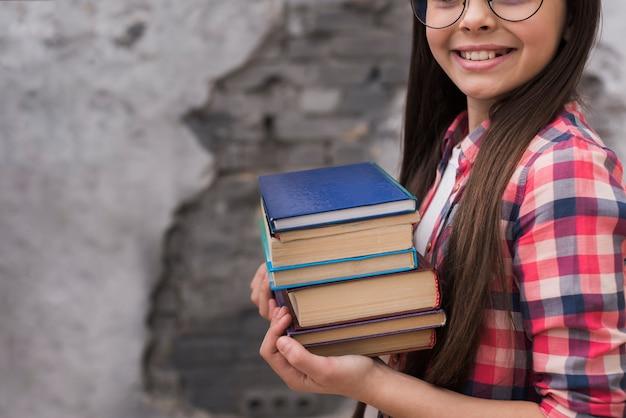 Close-up jovem garota segurando uma pilha de livros