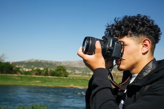 Close-up, jovem, homem, levando, fotos, dslr, câmera