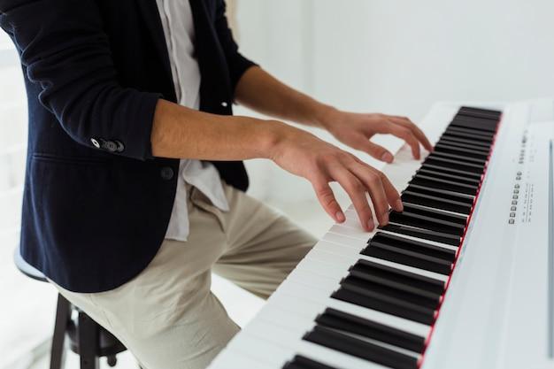 Close-up, jovem, homem, mão, tocando, piano
