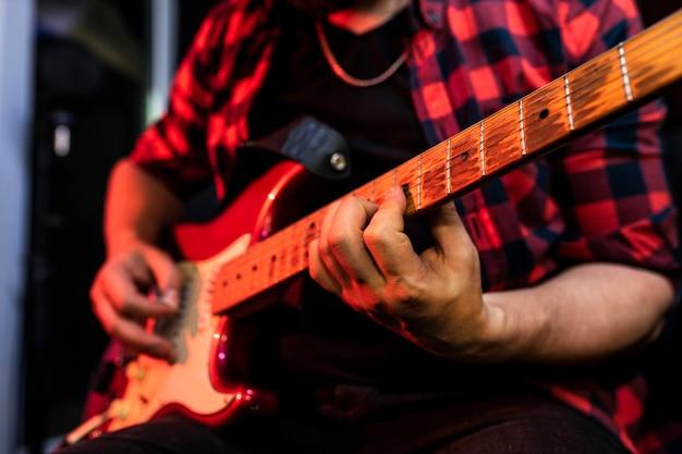 Close-up, jovem homem tocando guitarra elétrica no estúdio de gravação