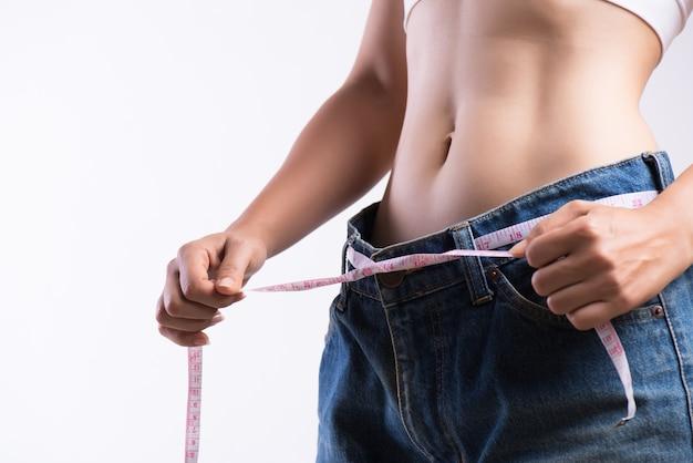 Close-up jovem magro, medindo sua cintura fina com uma fita métrica