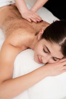 Close-up jovem morena recebendo uma massagem
