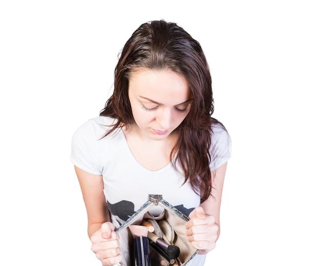 Close-up jovem mostrando suas maquiagens em um pequeno saco aberto para a câmera, isolado em um fundo branco.