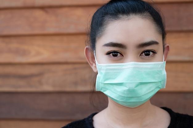 Close-up jovem mulher asiática colocando uma máscara médica para proteger das doenças respiratórias transportadas pelo ar como a gripe covid-19 pm2.5 poeira e poluição atmosférica na parede de madeira da parede