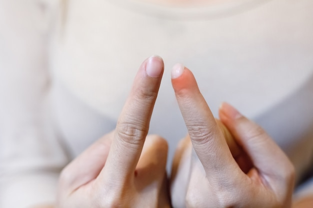 Close-up jovem mulher bonita tem dor no dedo indicador esquerdo.