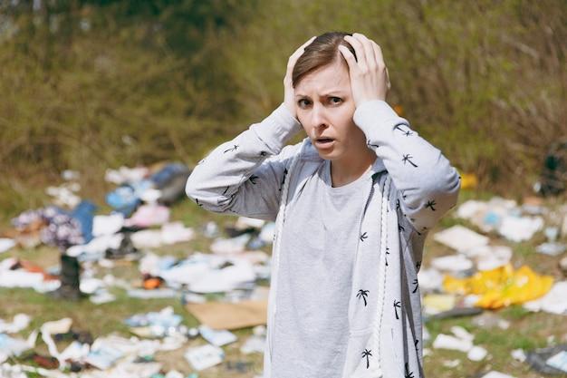 Close-up jovem mulher chocada com roupas casuais, limpando agarrado à cabeça perto de uma pilha de lixo em um parque cheio de lixo