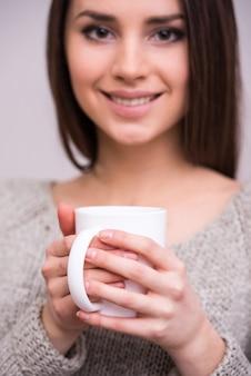 Close-up jovem mulher está segurando uma xícara de chá.