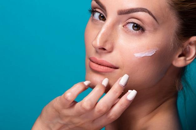 Close-up jovem mulher hidratando o rosto