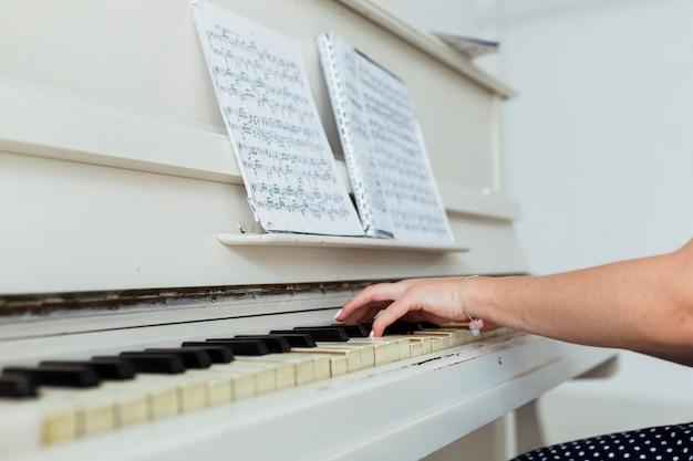 Close-up, jovem, mulher, mão, tocando, piano
