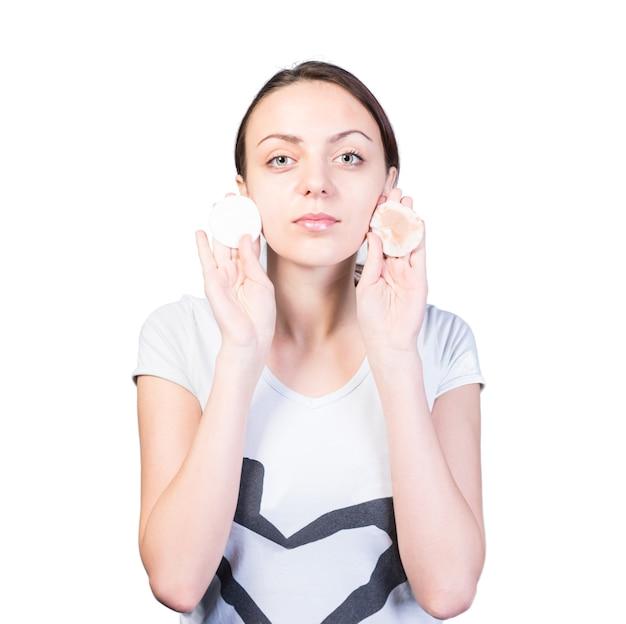 Close-up jovem mulher segurando algodões limpos e sujos perto de seu rosto enquanto olha para a câmera a sério, isolado em um fundo branco.