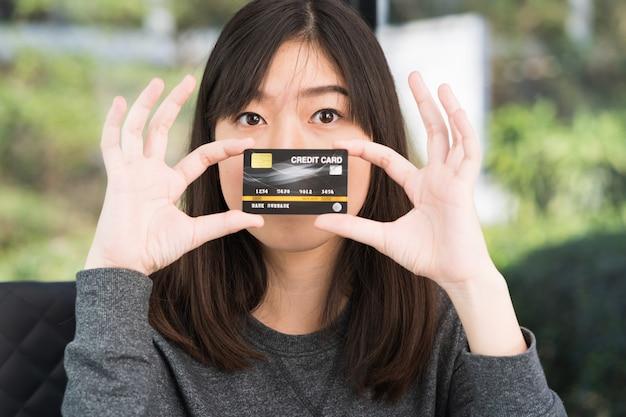 Close-up jovem mulher segurando o cartão de crédito