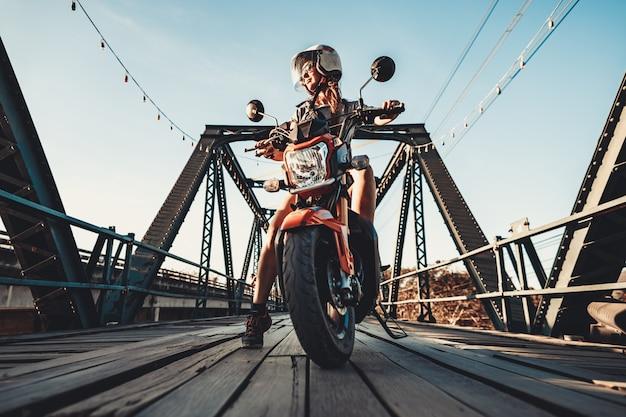 Close-up jovem mulher sentada na moto.