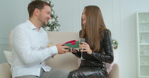Close-up jovem recebendo um presente de feriado do marido. menina bonita, abraçando-se com o namorado no natal, comemorando os feriados juntos.