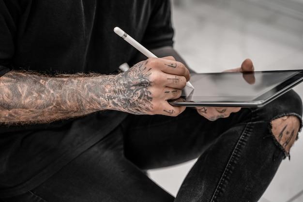 Close-up jovem tatuador de desenho a lápis e esboço em pé no local da oficina. foto do conceito de salão de tatuagem.