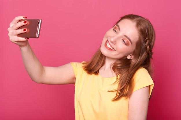 Close-up jovens mulheres elegantes fazendo selfie, usando seu próprio smartphone, vestido casual camiseta amarela, tem cabelos lisos, quer nova foto para redes sociais.