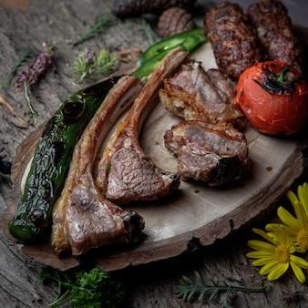 Close-up kebab costelas grelhadas lula kebab com tomate assado, pimenta em uma placa de madeira em uma casca de madeira escura