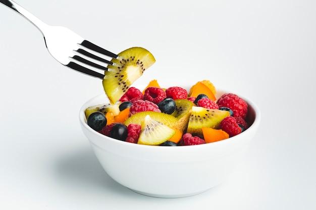 Close-up kiwi no garfo com tigela de frutas