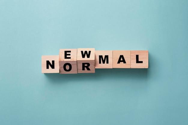 Close-up lançando cubos com palavras novo normal