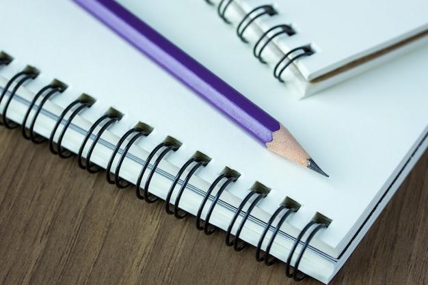 Close-up lápis e caderno espiral na mesa de madeira, ponto de foco seletivo