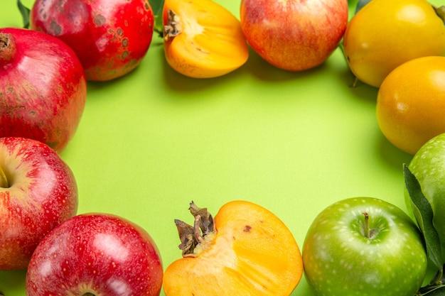 Close-up lateral com frutas coloridas romã maçãs caquis e folhas na mesa
