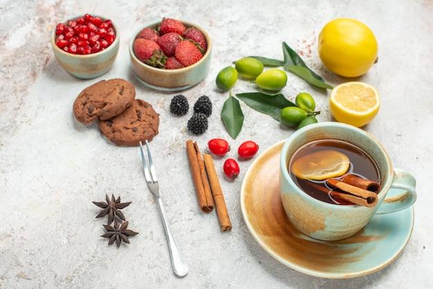 Close-up lateral com frutas cookies cookies de anis estrelado morangos xícara branca de chá frutas cítricas canela paus garfo na mesa