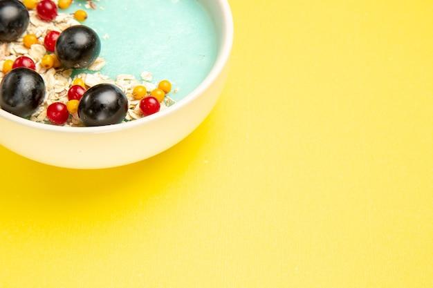 Close-up lateral com frutas e aveia na mesa amarela