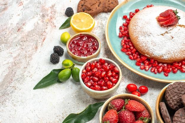 Close-up lateral com frutas, geleia de limão, bolo de romã com biscoitos de chocolate e morangos