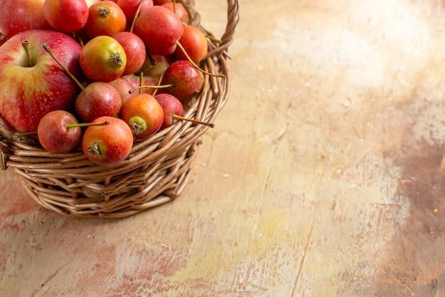 Close-up lateral com frutas, maçãs e frutas na cesta de madeira na mesa de creme