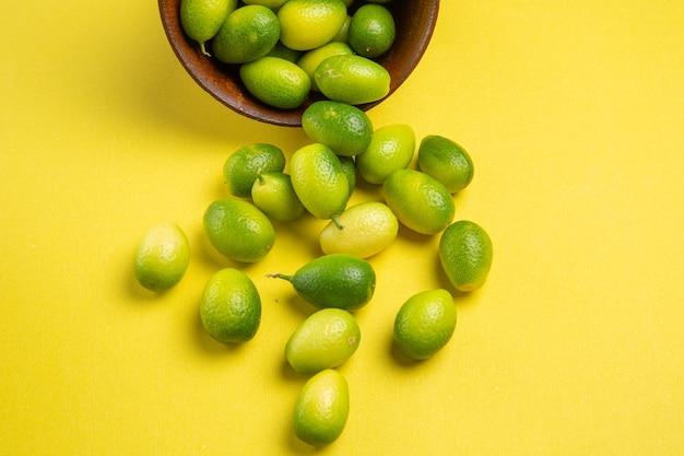 Close-up lateral da tigela de frutas verdes das frutas verdes apetitosas na superfície amarela