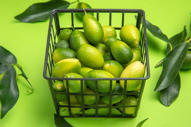 Close-up lateral de frutas cítricas cesta cinza de frutas cítricas folhas verdes na mesa verde
